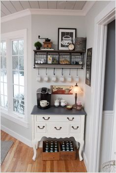"""Coffee Station. White coffee maker (left), small lamp (right), tray with coffee/teas (center), """"cup"""" print (behind tray). Print is saved on Going Home board"""