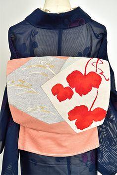 ほのかに柿色をおびた珊瑚のような淡い紅色に、大きな緋色の蔦葉あでやかに美しく浮かぶ色紙文様が織り出された大正浪漫・昭和レトロな詩情ただよう絽の夏の名古屋帯です。