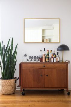 Midcentury modern inspired space with a bar cart below a gold mirror