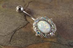 """White fire opal belly button jewelry ring with a band of ab crystals that surround the oval shaped opal. Will arrive in a gift box. The white opal belly ring is 14 gauge and 3/8"""" long, and is made of"""