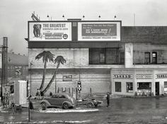 "December 1937. ""Gas station in Minneapolis."" The Minnesota tropics, where snow dusts the painted palms."