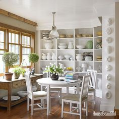 This kitchen combines an old Danish table and chairs with the extensive collections in the bookshelves.   - HouseBeautiful.com