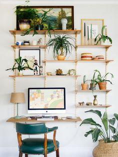 Muitas plantas e cachepots no home office com mesa de madeira e cadeira verde