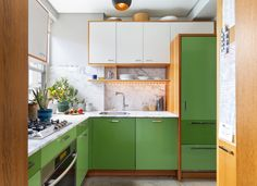 The kitchen cabinets in white, natural fir and two alternating shades of green inspired by Castelvetrano olives contrast with marble backsplashes.