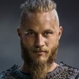 Vikings.  Ragnar Lothbrok is a restless young warrior and family man who longs to find and conquer new lands across the sea and claim the spoils as his own. Now he is an earl and with more power than ever before, his desire to sail west and explore new kingdoms remains unquenchable. Ragnar feels a deep affinity for the Norse god Odin. This powerful deity is the god of warriors slain in battle and is also the god of curiosity.  Played by Travis Fimmel