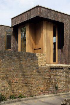 """Construite sur le site d'un ancien garage dans le quartier de Thorburn Square, à Londres, la maison épouse un mur existant en brique. Satish Jassal Architects décrit ce mur comme """"faisant intrinsèquement partie du lieu"""", il a donc été conservé et entoure ainsi la nouvelle maison. Le studio a voulu intégrer le mur pour ancrer la maison dans le site. Au final, ce dernier soutient un côté de la nouvelle structure. Le bâtiment est en retrait du bord de la rue et la partie inférieure de la… Brick Wall, British Architecture, Amazing Architecture, Journal Du Design, London House, Norman Foster, Le Site, House Extensions, Brickwork"""
