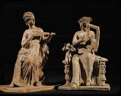 Woman on a rock with a violin and another with a large kithara, a little Eros at her side. Terracotta figurines from Aigina, Greece, Tanagrian influence (ca. 360 BCE). (Size of the musician 22 cm - CA 574) CA 798   Louvre, Departement des Antiquites Grecques/Romaines, Paris, France