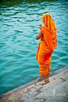 A woman offers prayers on the edge of the Ganges River in the ancient city of Varanasi or Benares Taj Mahal, Indiana, Amazing India, Indian People, Orange And Turquoise, World Photography, Varanasi, People Of The World, India Travel