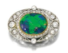 OPAL AND DIAMOND BROOCH, CIRCA 1910 The polished opal within an openwork border millegrain-set with circular-, single-cut and rose diamonds.