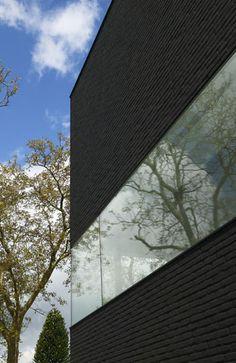 Woonhuis te Drongen: Een glazen band loopt op halve hoogte om het hele huis heen. Deze is zo hoog dat geen indiscrete blikken naar binnen kunnen worden geworpen vanaf de openbare weg die langs het huis loopt.