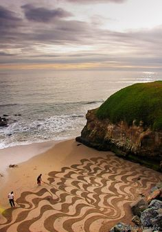 San Francisco artist Andres Amador uses the beach as his canvas, racing against the tide to create these large scale temporary pieces using a rake or stick.