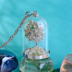Exquisite silver jewelry of a tiny bell jar terrarium containing an exotic silver and gold leaved miniature tree studded with tiny emeralds and