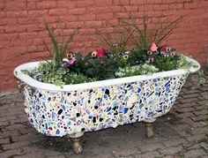 Old vintage tub with ceramic pieces put on it and then turned into a planter for flowers and plants!
