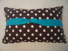 brown, long, super cute pillow with white polka dots and a turquoise bow!