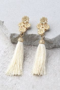 Every day is a beautiful day with the Beneath the Flowers Gold Tassel Earrings! Clusters of textured gold flowers top fun beige tassels. Earrings measure 3.5 tall.