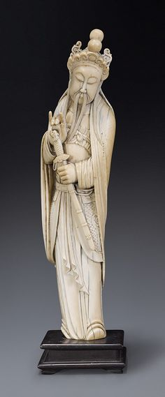 An ivory figure of Guandi Qing dynasty, 18th/19th century  standing with head slightly lowered looking at the sword clasped in his left hand, wearing an elaborate helmet and long cloak draped over his armour and loose robe beneath, his face with long side whiskers, moustache and beard, wood stand  30.5 cm high