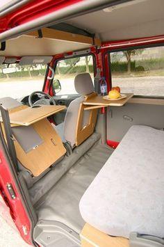 Jeder Platz wird clever genutzt. Klapptische an den Rückseiten der Sitze in einem Camper-Bus.
