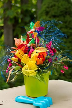 Beautiful summer centerpieces with a bucket and sand shovel (would double as a great favor)