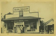 Photo of Glen Valley General Store, located in Glen Valley, Saskatchewan, in what is now called Disley, Saskatchewan. The store is in the chain of Red & White Stores, provides Union gasoline, Triton motor oil, Good Year tires, and Sweet Capral cigarettes. A group of six people stands in front of the store.