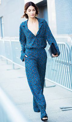 A patterned V-neck pantsuit is worn with a simple black clutch.