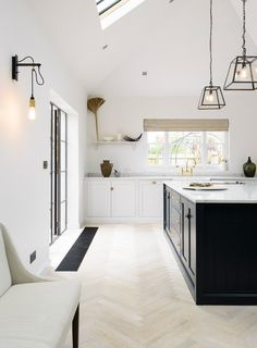 Breathtaking neutral white modern farmhouse kitchen with dark blue island, creamy cabinetry, and Seapearl parquet flooring. Modern exposed bulb pendant lights, skylight, and minimal decor. Design by Devol. Devol Kitchens, Shaker Style Kitchens, Modern Farmhouse Kitchens, Farmhouse Kitchen Decor, Home Decor Kitchen, Home Kitchens, Kitchen Design, Modern Shaker Kitchen, Devol Shaker Kitchen