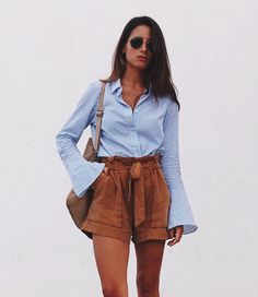 This blue button up shirt with wide sleeves looks divine with these loose fitted brown shorts. Love the contrast between these two #summer outfit pieces.