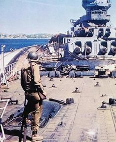 American soldier on the deck of the destroyed French battleship Strasbourg in Toulon, August 1944. Near the battleship on its side is the light cruiser La Gallissoniere.