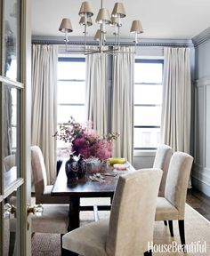 """The dining room is """"crisp, clean, relaxed, and very Zen,"""" Doherty says. The Belgian linen curtains and the suede upholstery on the Intérieurs Charlotte chairs were dyed to match the walls, painted Farrow & Ball Pavilion Gray."""