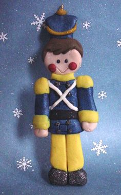 Polymer Clay handcrafted Christmas Ornament . This little Guy is dressed like a Wooden Soldier in Blue and Yellow.  Great for a First