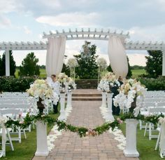 Simply stunning wedding ceremony floral by Atmospheres at the beautiful Royal Crest Room in St. Cloud, Florida south of Orlando. Love the pergola at this wedding location! #orlandowedding #floridawedding #weddingdecor
