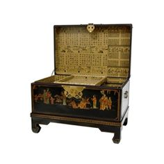 This black lacquered keepsake trunk features fine, hand-painted Ming era art motifs and a rich, black lacquer finish. A traditional wedding or anniversary gift in both the Far East and the West, this chest features decorative brass handles at each end, and a lacquered brass butterfly hasp. It also comes with a decorative, four-legged display stand with gold, geometric border design.