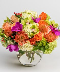 Enchanted Blooms - A luxurious arrangement of exotic orchids, hydrangea, roses and protea in vivid oranges, greens, peaches and purples is presented in an elegant glass bowl.