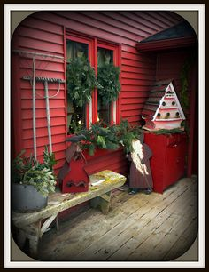 primitive exterior; red house with country/primitive pieces - bench, birdhouses, santa; lots of greenery on windows; antique tools