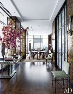Structural columns along the apartment's perimeter were sheathed in Indian mica, as were a number of the walls, adding to the home's glamour and warmth. In the wide corridor between the living and dining rooms, bronze-and-glass doors leading to the kitchen were custom made by Josette Trublard and are flanked by sconces from JF Chen; at left, a sixth-century Chinese sculptural fragment and a pair of circa-1900 Japanese bronze geese are displayed atop a midcentury mirrored table in the style…