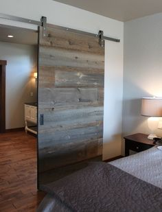 From the bedroom to the bathroom. LOVE this reclaimed barn wood sliding door!