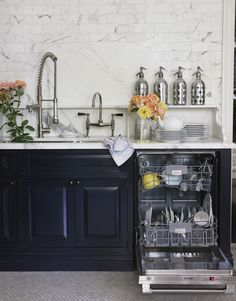 Okay! last picture of this kitchen! i love the marble counter tops w/ the black cabinets & stainless steel appliances and fixtures. The flowers add the perfect touch of color to warm it up.