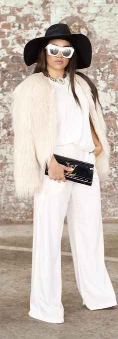 Australia street style inspiration for Spring / Summer: white wide-leg pants, a white furry jacket and white sunglasses with a black Louis Vuitton clutch and black wide-brimmed hat.