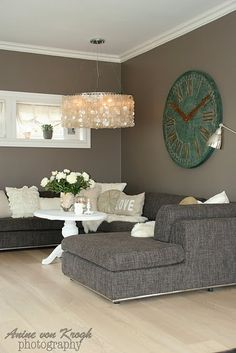 Oversized clock, capiz shell chandelier. Grey walls. Grey lounge with chaise.