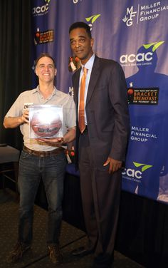 "Panelist Ralph Sampson presented Piedmont CASA Volunteer Jon Emm with a basketball signed by Tony Bennett, Head Coach of the UVA Men's Basketball Team. ""Jimmy Miller's Bracket Breakfast for Piedmont CASA"" on March 14, 2016. Image by Jennifer Byrne Photography."