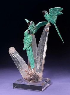 <i></i><i>By Peter Mueller<br />Brazil</i><br />Three tropical birds alight upon an impressive rock crystal quartz cluster. Carved of brilliant bluish-green Brazilian amazonite, their cheeks are inset with white agate and onyx, the beaks are carved of garnet and the tongues of coral. A stately and vibrant composition sure to grace any interior. <br /><i>Height 19in </i>