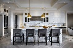 For a Toronto-area home, designer Ferris Rafauli controlled every aspect of the building process, from conceiving the interiors to building the custom furniture to designing the landscaping, and blended contemporary details with classic elements. Calacatta marble and shiny brass fittings lend a sense of opulence in the kitchen.