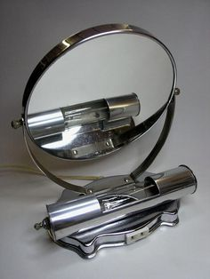 30's Art Deco / Machine Age table top shaving / make up mirror  30's Art Deco / Machine Age table top shaving / make up mirror with added power outlet for razor, etc.. Flip over mirrors for normal or magnified, uses a tube bulb. Chromed steel and aluminum.