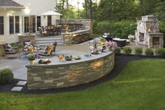 Outdoor space including a fireplace, lower patio seating area, raised patio seating area, lighting, and landscaping work.