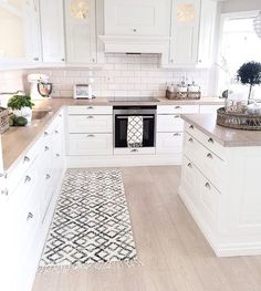 Vintage modern kitchen idea - the white cabinets, subway tiles and light countertops and flooring give this kitchen design a light and airy look.