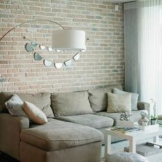 The Glitter Guide - living rooms - exposed brick wall, gray, leather, Moroccan, pouf, arc, lamp, Parsons Coffee Table, white parsons coffee table, exposed brick wall, beige sectional, beige sectional sofa, Pottery barn Sofa with Chaise Lounge, West Elm Parsons Coffee Table -White, Gray Leather Moroccan Pouf,