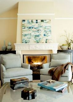 Cozy fireplace for the winter, with engaging abstract art on the fireplace mantel. Via CentsationalGirl blog.