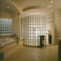 """Walk-in, door-less radius Glass Block Shower constructed with 6""""x8"""" Pittsburgh Corning Glass Block in the Decora Pattern and finished with an Endblock. The prefabricated vinyl framed Glass Block window also uses 6""""x8"""" Decora Glass Blocks to bring in light and maintain a moderate level of privacy above the large soaking tub."""