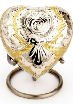 This small heart keepsake engraved with a detailed gold & silver design has been hand casted and intricately hand designed by skilled artisans. It has a nickel and gold engraved finish. A token amount of ashes can be safely placed in the keepsake via a threaded secure lid at the back.