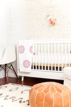 safari chic nursery decor with leather pouf and Eames chair.