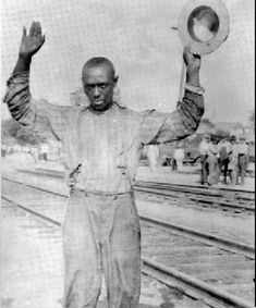 """In this image a Black man from Tulsa, Oklahoma raises his hands in surrender. In the aftermath of the Tulsa race riot, Black Tulsans soon found themselves subject to arrest by Tulsa officials and """"Special deputies."""" Photo credit: Bob Hower"""
